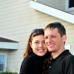 New homeowners posing in front of their house