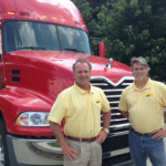 Tom and Ken agents with Paramount Insurance Agency posing in front of truck