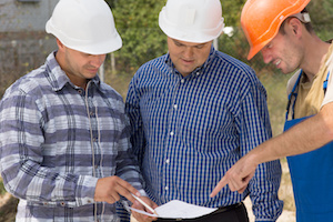 A manager, foreman, and skilled contractor wearing hard hats and reviewing the site plans on a construction site