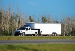 A white medium duty pickup truck towing a long dual axle trailer attached by fifth wheel commonly used by hot shot truckers